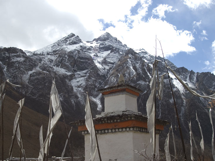 A view of a chorten, prayer flags, and a mountain in Bhutan
